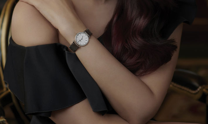 A woman is wearing a Longines watch